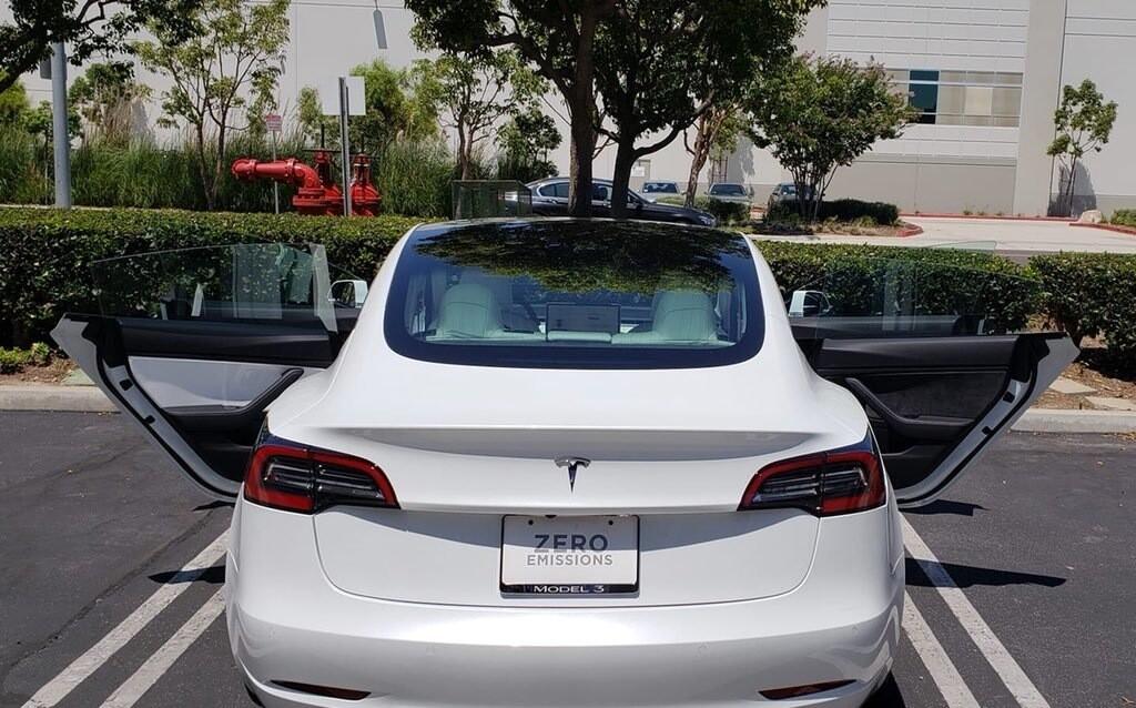 Tesla 3 с белым салоном и одной коричневой дверью